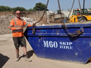 m60 skip hire blue skip attached on chains with worker beside it