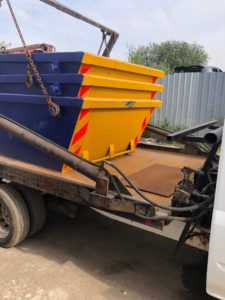 m60 three skip hire blue-yellow skips stacked up