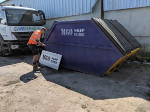 m60skiphire blue skip with worker at the left side