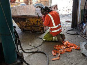 m60 skip hire worker in uniform fixing a skip