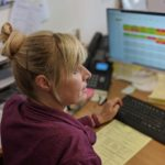 blonde woman facing at the side of the computer