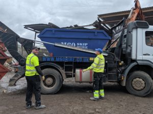 two men in the truck with skip hire