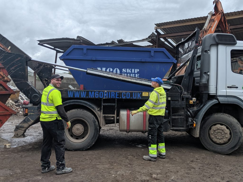 two men in the truck with blue skip hire