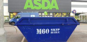 skip color in blue in front of asda building